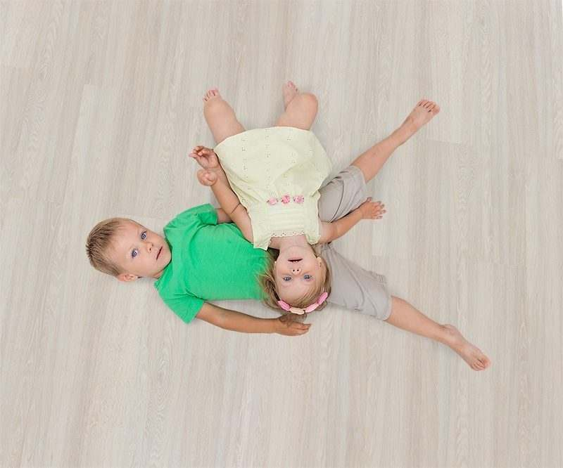 ash wood fusion cork floor boy and girl lying on the warm floor playing at home