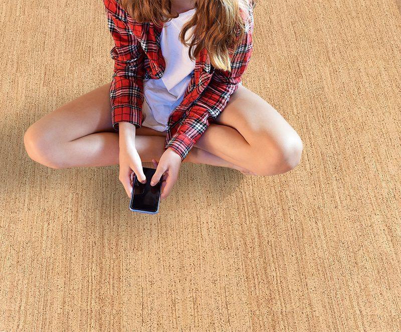 berber cork floor forna warm comfortable to walk bared feet teenage girl sitting on floor Best Flooring For Allergies
