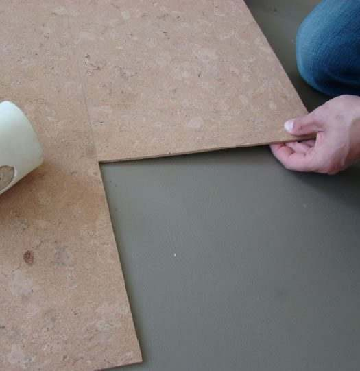 lay down cork tiles knock tightly rubber hammer.