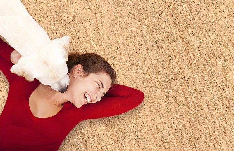 silver birch woman lying on the warm cork floor and her dog licking her face waterproof flooring for pets