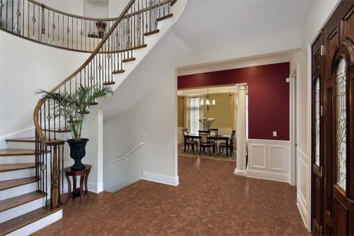 tasmanian burl forna cork floor foyer luxury home curved staircase view